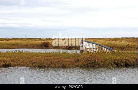 An old grounded clinker built boat by creeks in salt marshes on the North Norfolk coast at Morston, Norfolk, England, United Kingdom, Europe. - Stock Image
