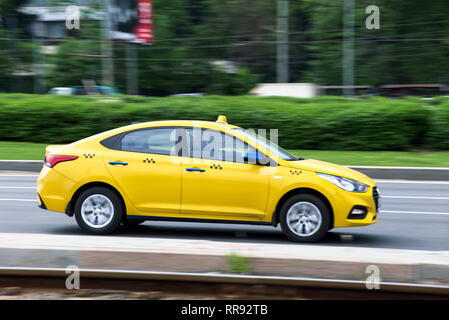 Russia, Moscow - May 13, 2018: Motion city street scene with a yellow taxi - Stock Image