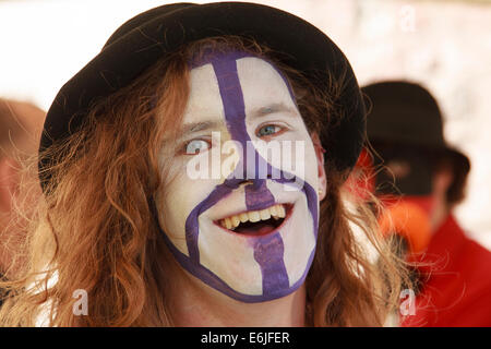 Smiling, long haired, teenage boy - face painted with CND symbol. - Stock Image