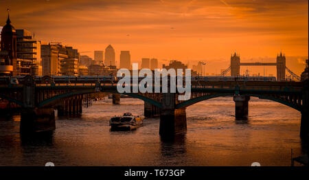 Sunrise over The River Thames and Southwark Bridge with Tower Bridge and Docklands, Canary Wharf in the distance. - Stock Image