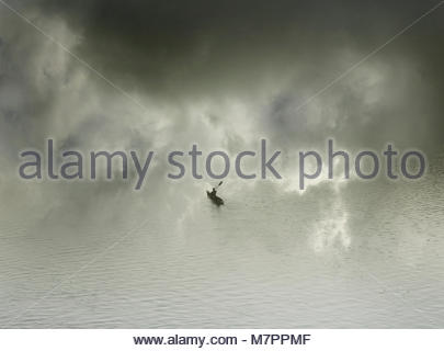 Man alone in kayak in fog - Stock Image