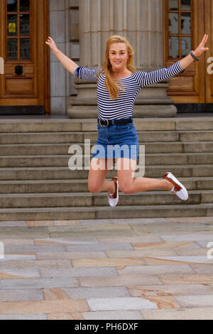A young woman with long blond hair having fun jumping high up in the air at the Caird Hall steps in Dundee, UK - Stock Image