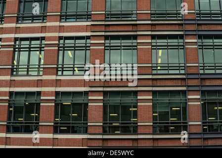 Typical office building exterior, mixing the modern French reinforced windows with traditional English brick wall buildings - Stock Image