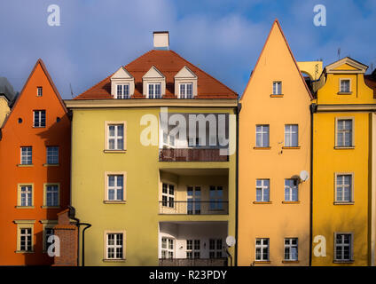 Colorful polish apartment buildings with pointy roofs.  Pastel colored narrow buildings, with a blue sky - Stock Image