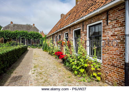 A cobblestone path runs beside brick residences in the village at Vesting Bourtange, the star-shaped fortress in Groningen Province, The Netherlands. - Stock Image
