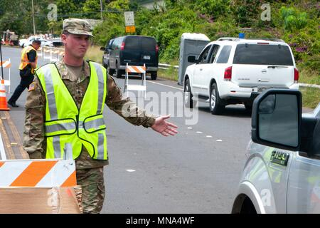 Air Force Spc Donavan Wills, a combat engineer with the 227th Brigade Engineer Battalion, directs traffic in response to the Kilauea volcano eruption at Leilani Estates May 12, 2018 in Pahoa, Hawaii. The recent eruption continues destroying homes, forcing evacuations and spewing lava and poison gas on the Big Island of Hawaii. - Stock Image
