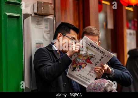 London, UK, 10 February, 2019. A Chinese man reading China Minutes newspaper during Chinese New year celebration at China Town, SOHO, London, UK. Credit: Harishkumar Shah/Alamy Live News - Stock Image