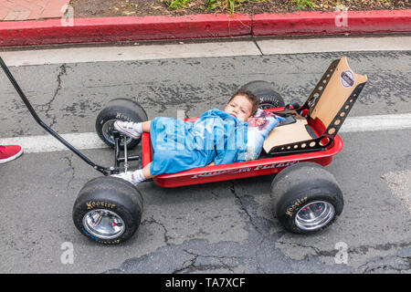 A Hispanic toddler lays down in a red Radio Flyer custom kids wagon as he is pulled along State Street at the Nationals Premier Car Show in Santa Barb - Stock Image