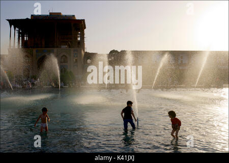 Kids playing in the public fountains in front of Ali Qapu Palace, Imam square. Naqsh-e Jahan  Isfahan city, Iran - Stock Image