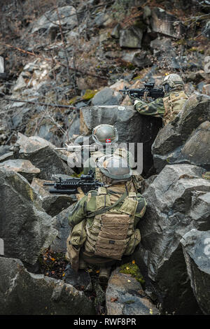 Norwegian rapid reaction special forces FSK soldiers among the rocks guarding perimeter. - Stock Image