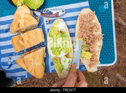 Avocado and tuna bocadillo/sandwich being prepared at outdoor picnic in Spain. - Stock Image
