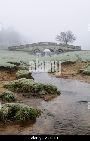 Hovingham Beck flowing under an ornate stone bridge and cascading over a small weir, on a misty morning in Hovingham - Stock Image