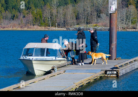 Four young people and a dog climbing on board a moored boat in Grant Narrows Regional Park, Pitt Meadows, British Columbia, Canada - Stock Image