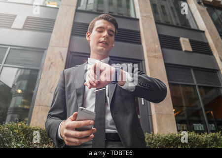 Close up of businessman next to business center at downtown holding mobile phone in hand and looking at watches. Bottom view - Stock Image