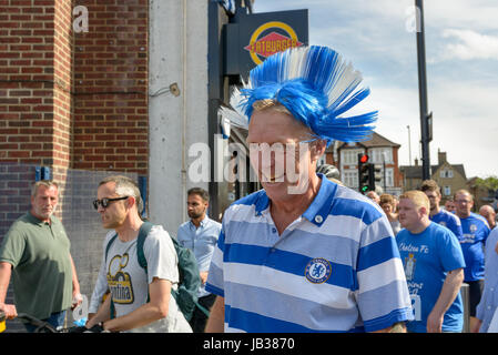 Chelsea fan with a wig in club colours walks to Wembley stadium for the FA Cup Final 2017 Arsenal vs Chelsea. London, - Stock Image