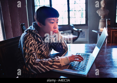 Young modern woman and computer in classic Tuscan villa - Stock Image