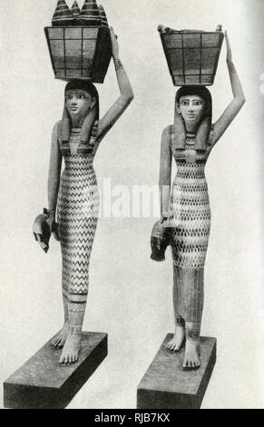 Wooden statues of handmaidens with baskets on their heads, discovered near Thebes during excavations, Egypt. Their purpose was to minister to the needs of the dead inside a pyramid. - Stock Image