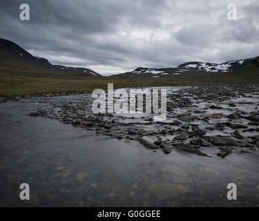 River flows through rugged mountain landscape, near Tjäktja hut, Kungsleden trail, Lapland, Sweden - Stock Image