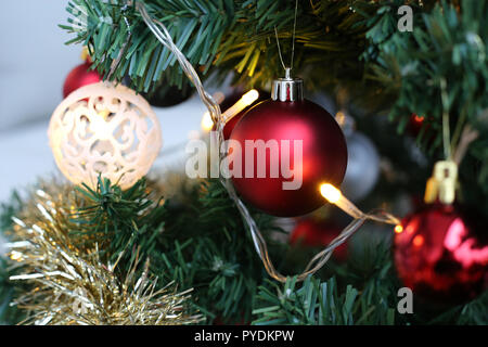 Closeup of a Christmas tree with some beautiful ornaments in it. Very traditional and cozy Christmas photo with warm and welcoming colors. Merry Xmas! - Stock Image