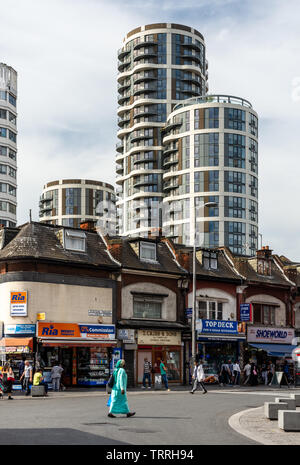 London, England, UK - June 1, 2019: Pedestrians walk past independent shops on Station Parade in Barking Town Centre, with new build high-rise apartme - Stock Image
