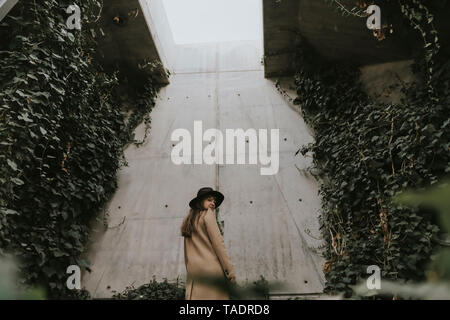 Young woman in underground tunnel, concrete wall full of plants - Stock Image