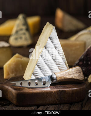 Segment of  Brie cheese or soft cow's - milk  French cheese on wooden board. Different cheeses at the background. - Stock Image