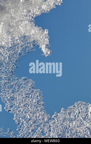 Close up of snow that has melted in the spring sunshine until only a thin, transparent sheet of ice is left through which you can see the blue sky. - Stock Image