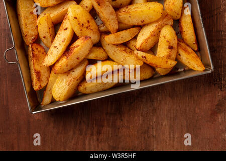 Potato wedges, oven roasted, close-up shot from above in a baking tray on a dark rustic wooden background with a place for text - Stock Image