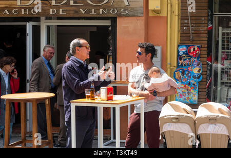 Man making a double thumbs up gesture to his son and granddaughter outside a bar in Seville - Stock Image