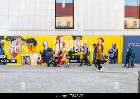 Vienna Austria art, view of Viennese people walking past a colourful Leopold Museum advertisement celebrating modernist art in 1900 Vienna, Austria. - Stock Image