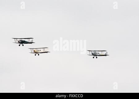 Three biplanes in flight against an overcast sky at the Tyabb airshow in Victoria, Australia. De Havilland Tiger - Stock Image