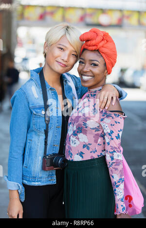 Portrait smiling, confident young women friends hugging - Stock Image