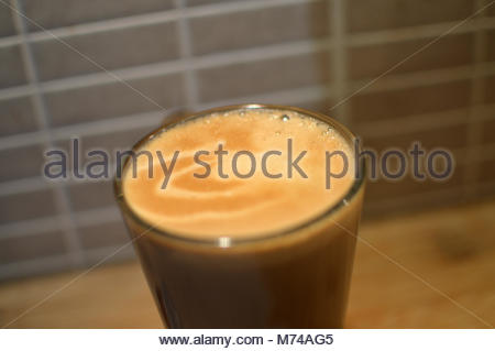 Closeup of white coffee in tall glass with milk and foam. Used coffee pod on wooden table next to glass - Stock Image
