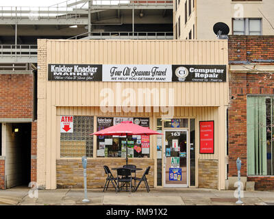 Urban small business and market front exterior with a table and a red umbrella on the sidewalk in Montgomery Alabama, USA. - Stock Image