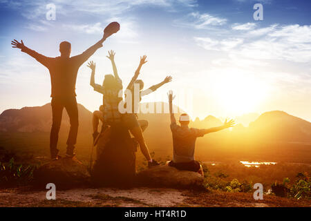 Group friends sunrise mountains happy - Stock Image
