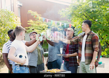 Happy male friends toasting drinks over barbecue grill in backyard - Stock Image