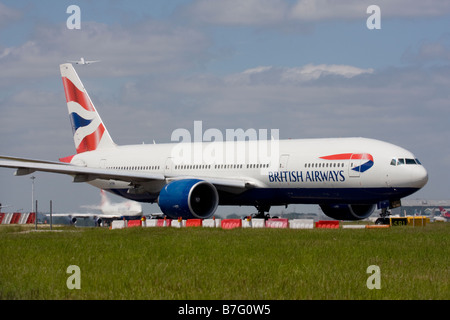 British Airways Boeing 777-236/ER and another commercial airplane taking off in the background at London Heathrow - Stock Image