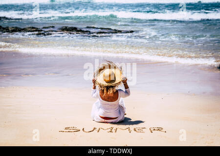 Summer holiday vacation concept for beautiful trendy caucasian girl sit down on the sand at the beach enjoying the freedom of the ocean in front - peo - Stock Image