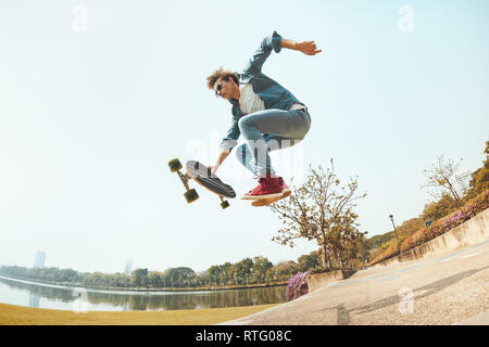 Man hipster jumps with skateboard in park - Stock Image