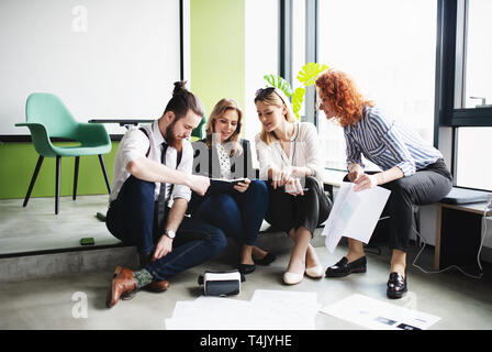 A group of young business people with a diary sitting on the floor in an office, talking. - Stock Image
