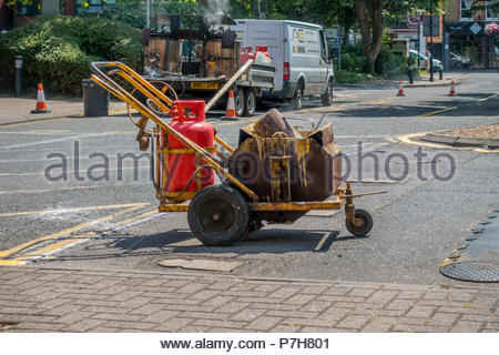 Hot paint line marking machine loaded with yellow paint ready to repaint a box junction. - Stock Image