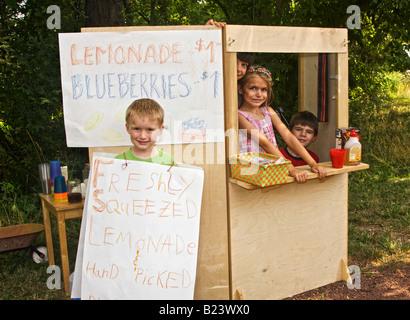 young Children selling Lemonade at homemade lemonade stand - Stock Image