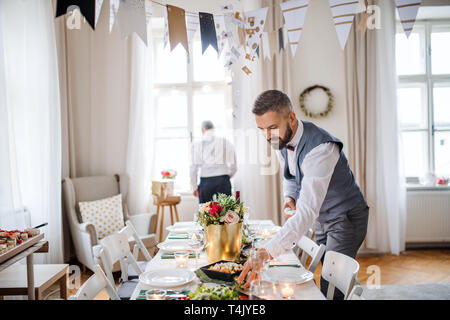 A portrait of a senior and hipster mature man standing indoors in a room set for a party, talking. - Stock Image