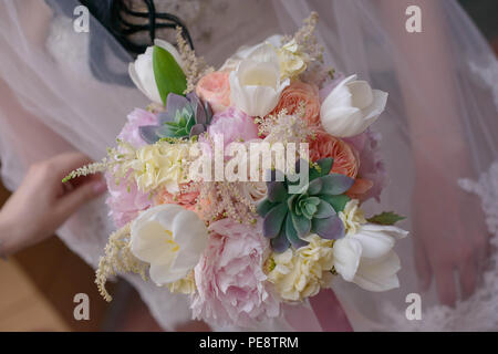 Close-up on Caucasian woman's hands holding an elegant bridal bouquet, with soft, pink hues - Stock Image