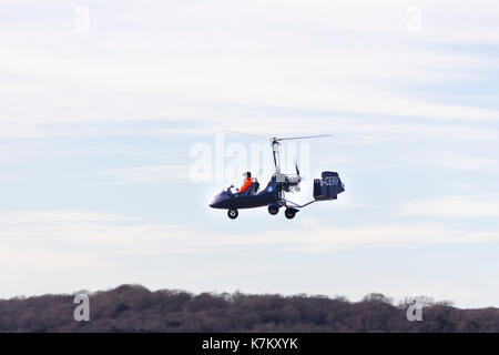 A Rotorsport UK MT-03 gyrocopter flying low over the River Kent estuary an Arnside, Cumbria. The MT-03 is version of the German built AutoGyro MT-03,  - Stock Image