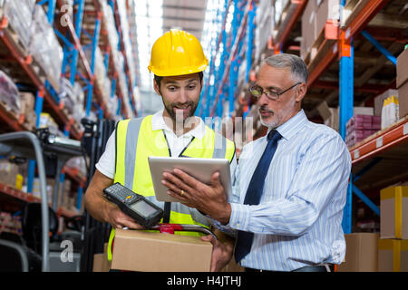 Warehouse manager with interacting male worker over digital tablet - Stock Image