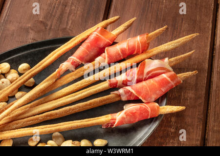 Prosciutto-wrapped Italian grissini with roasted almonds, close-up on a dark rustic wooden background. Italian antipasti with parma ham - Stock Image