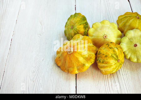 Six yellow and green bush pumpkins on white wood background. Garden,agriculture and farming concept. - Stock Image