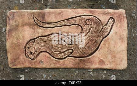 Decorative ceramic tile showing playful otter at RSPB Leighton Moss Reserve, Lancashire, UK - Stock Image