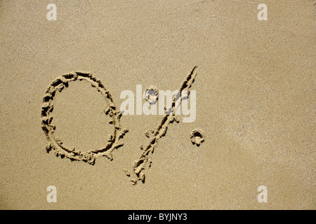 '0%' written out in wet sand. Please see my collection for more similar photos. - Stock Image